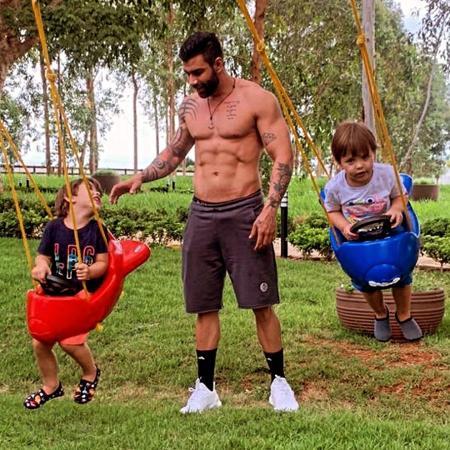 Gusttavo Lima posa sem camisa e mostra tanquinho em parque com os filhos